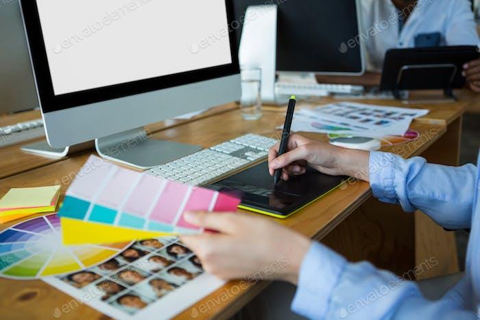 Primer plano de la diseñadora gráfica Mujer Uso la tableta Gráficos en el escritorio