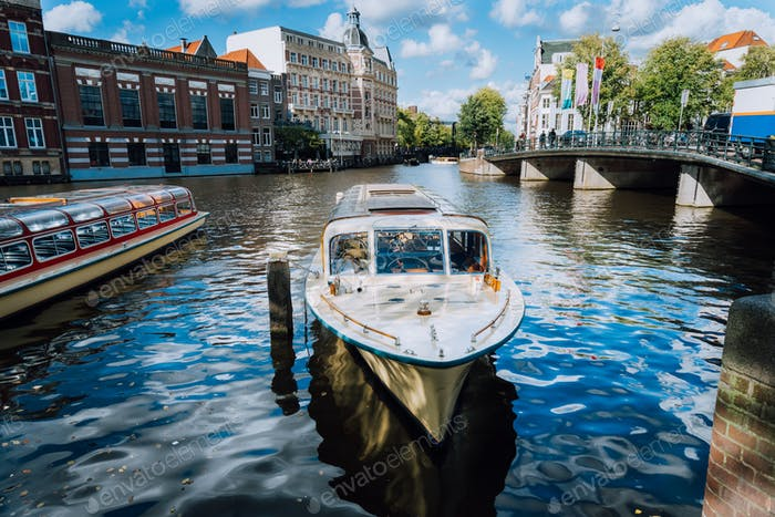 View on the bridge through the river channel with boat in front, typical picture of canals in