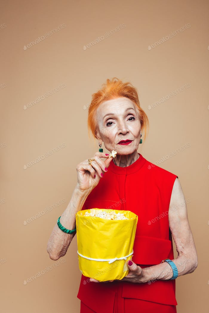 Amazing mature redhead fashion woman eating popcorn