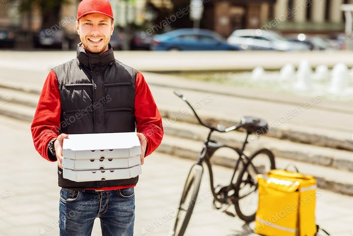 Delivery Courier Holding Pizza Boxes Smiling To Camera Standing Outside