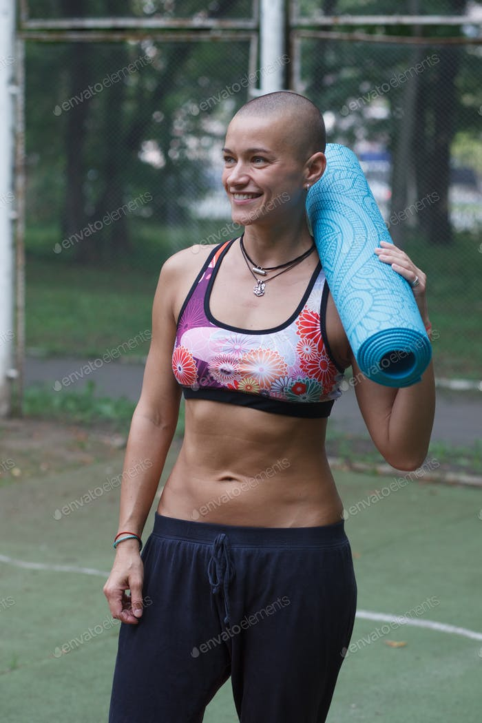 athletic woman with yoga carpet