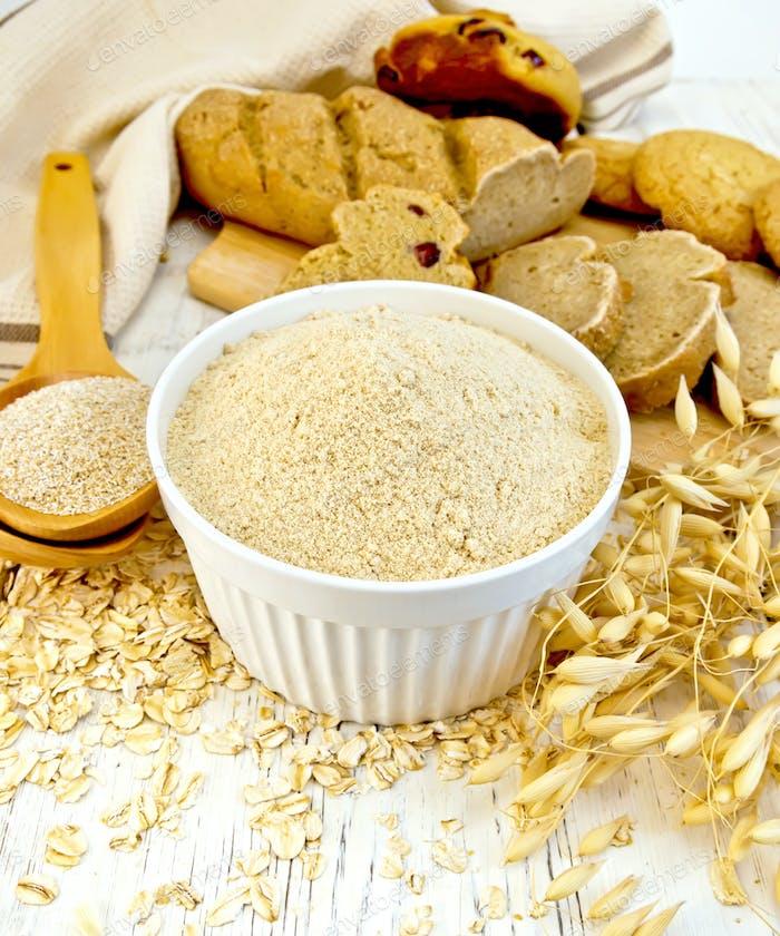 Flour oat in white bowl with bran in spoon on board