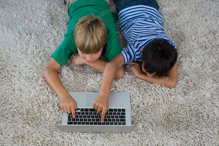 Siblings lying on rug and using laptop in living room
