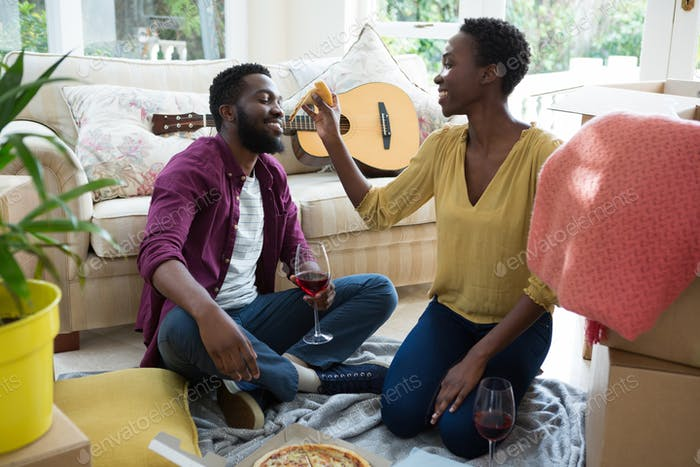 Couple having pizza in new house