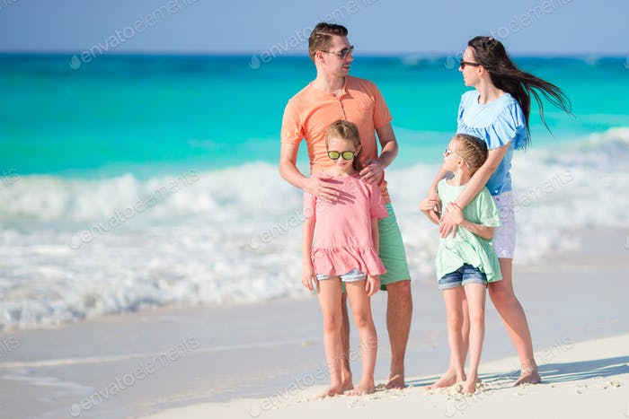 Happy beautiful family of four on a tropical beach
