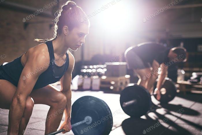 Muskulöser Mann und Frau heben schwere Langhanteln