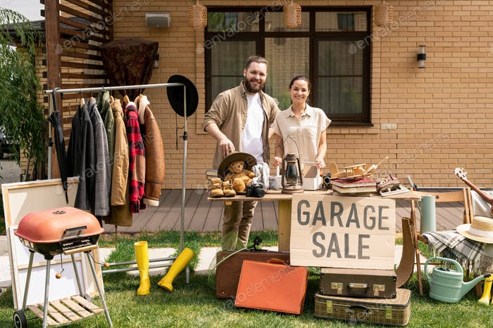 Cheerful couple hosting garage sale