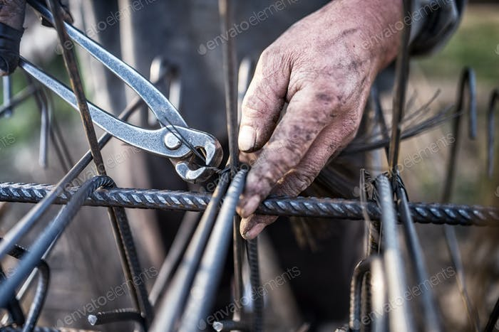 Details of construction worker - hands securing steel bars with wire rod