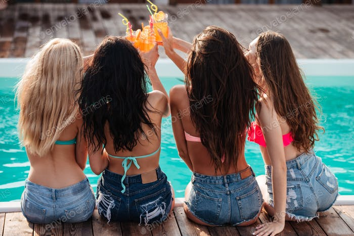 Attractive women celebrating and toasting at party near swimming pool