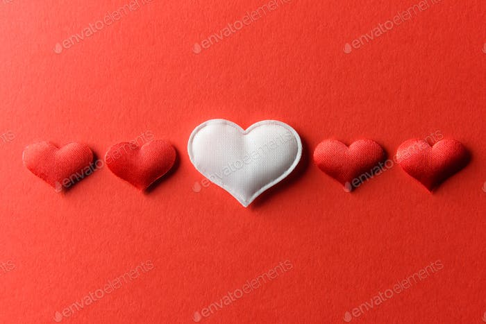 Red and white textile hearts on red paper