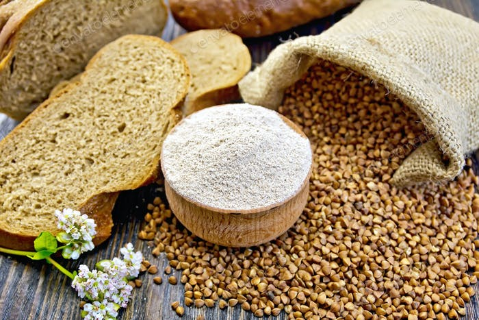 Flour buckwheat in bowl with grains on board