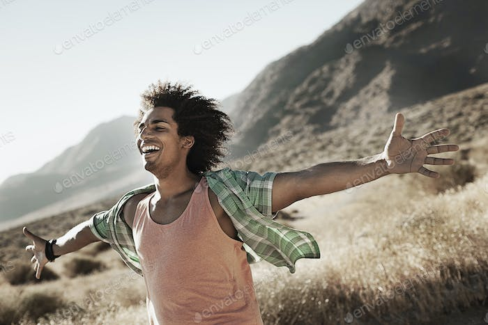 A man standing with arms outstretched in a breeze
