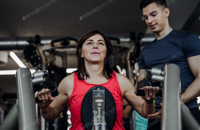 A female senior with a young trainer doing strength workout exercise in gym.