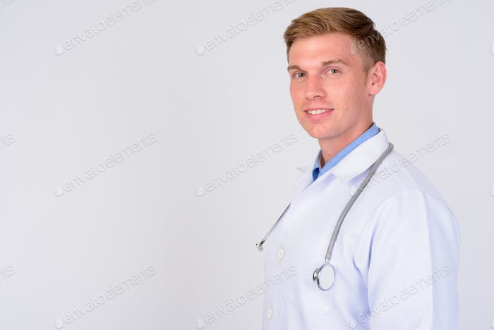 Profile view of happy young man doctor with blond hair looking at camera