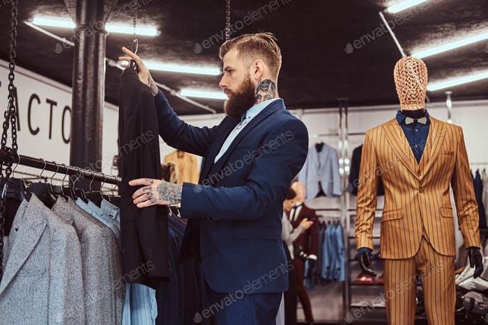 Elegantly dressed bearded male with tattoos on hands and neck chooses new suit in a menswear store.
