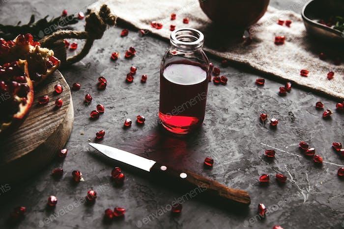 Roter Granatapfelsaft in einem Glas, reif und geschnitten Granatapfel und ein Zweig Minze auf einem grauen Beton