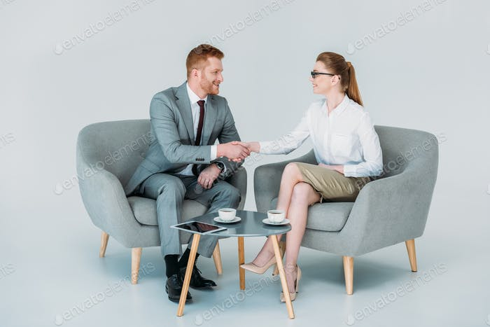 businessman and businesswoman shaking hands while sitting in armchairs, isolated on white
