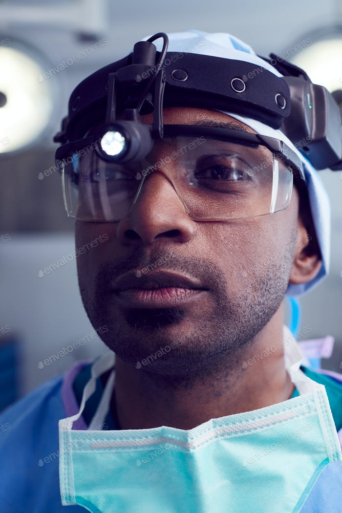 Portrait Of Male Surgeon Wearing Protective Glasses And Head Light In Hospital Operating Theater