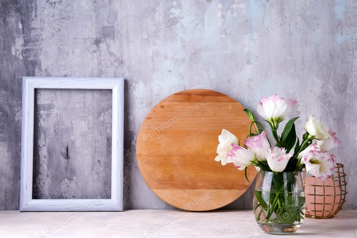 Eustoma flowers in vase on table near stone wall, space for text. Blank for postcards