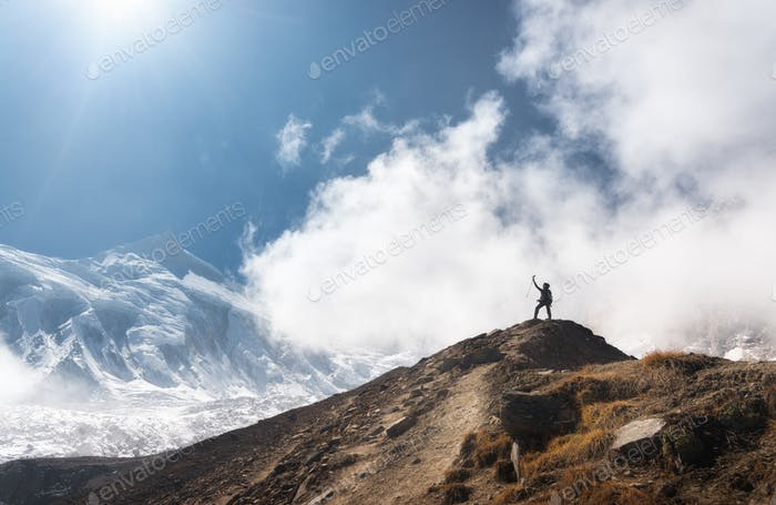 Young woman with raised up arms on the mountain peak