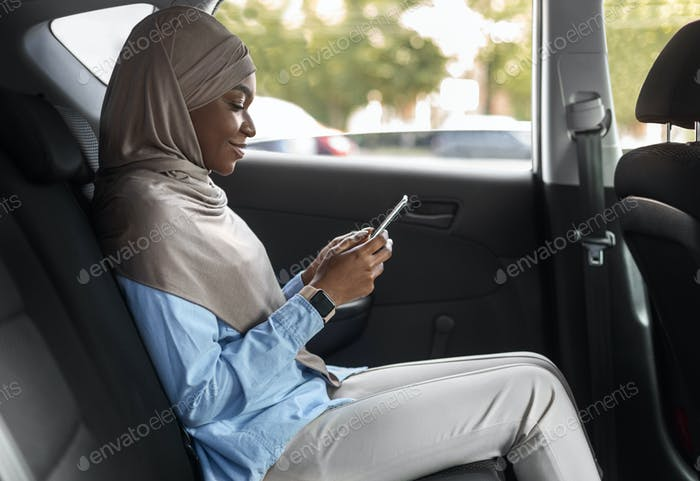 Smiling Black Muslim Female Entrepreneur Browsing Smartphone While Riding Car On Backseat