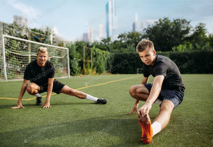 Male soccer players doing stretching exercise