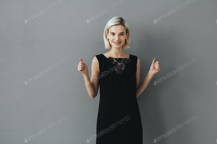 Wooman thumbs up success happy female portrait over gray background