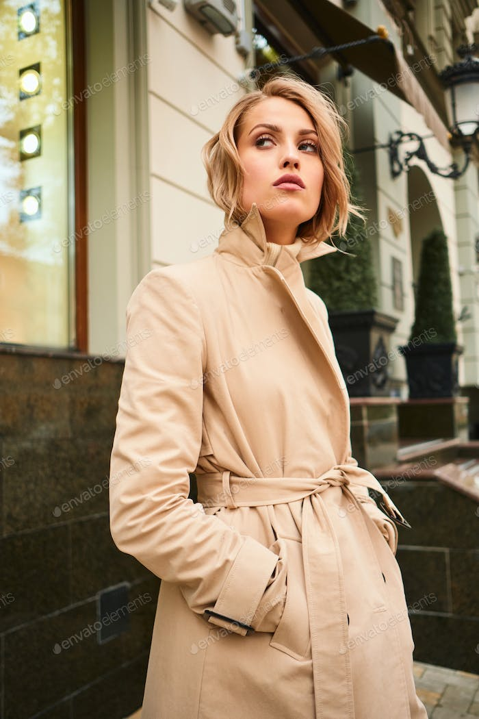 Beautiful serious stylish blond girl in beige coat confidently looking away on city street