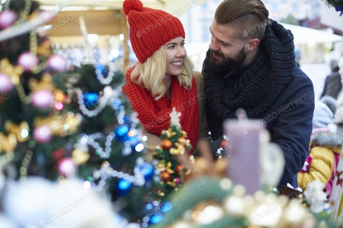 Couple outdoors surrounded with Christmas ornaments