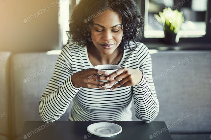 Young African woman enjoying a fresh cup of coffee