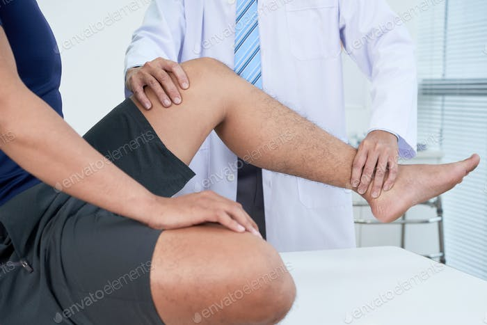 Doctor checking leg of patient