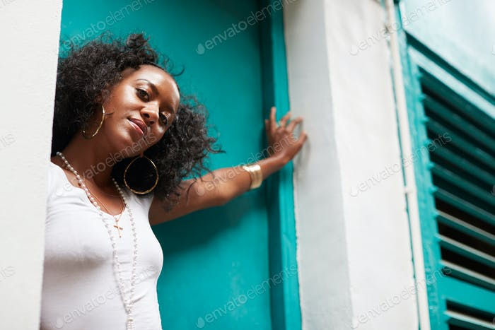 Young black woman leaning in a doorway, low angle, close up