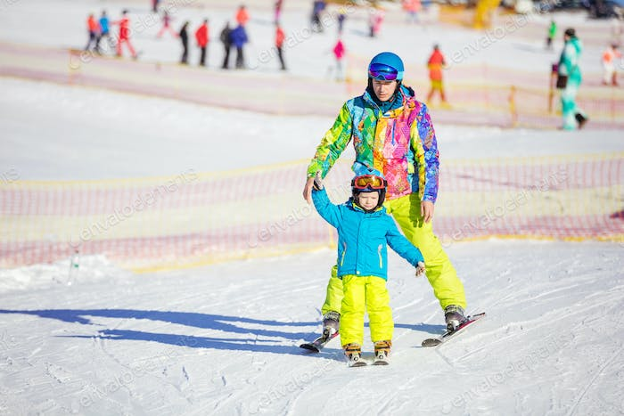 Father ior instructor teaching little boy to ski