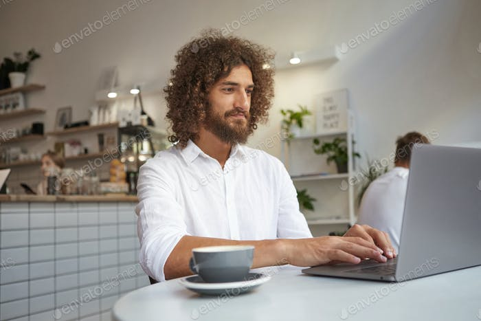 Indoor portrait of pretty young curly man with beard reading good news on his laptop