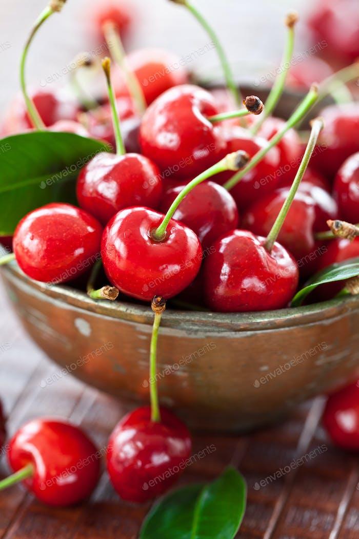 Fresh cherries in vintage copper cup