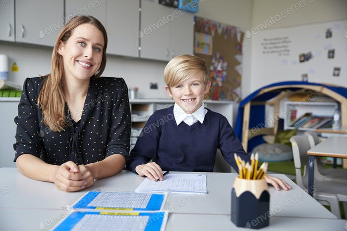 Young female primary school teacher and schoolboy sitting at a table