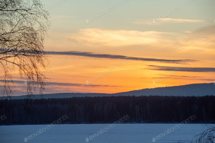 Beautiful scenery of sundown on frosty winter evening in the countryside