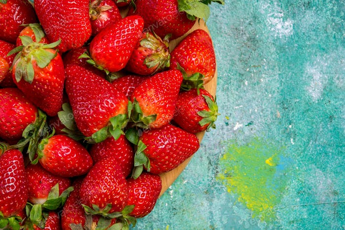 Fresh strawberries on painted wooden table