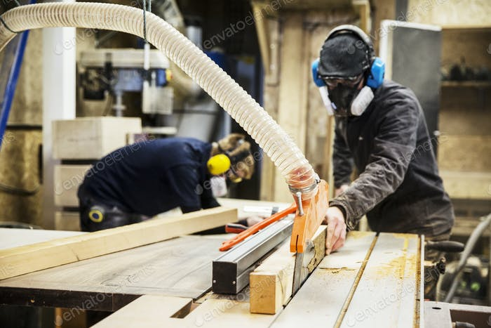 Man wearing ear protectors, protective goggles and dust mask standing in a warehouse, cutting piece