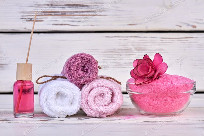 Still life rolled terry towels with pink salt and body oil.