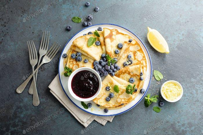 Crepes, dünne Pfannkuchen mit Blaubeermarmelade und frischen Beeren mit Zitronenschale