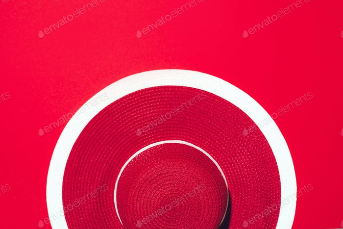 Top view of red striped retro hat over paper background with copy space. Summer travel and holiday