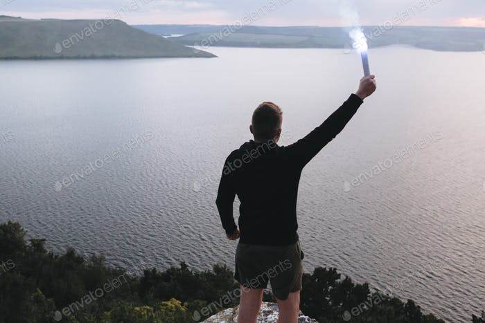 Ultras hooligan holding blue flare torch in hand, standing on top of rock mountain