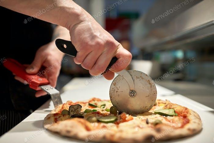 Kochen schneiden Pizza in Stücke in Pizzeria