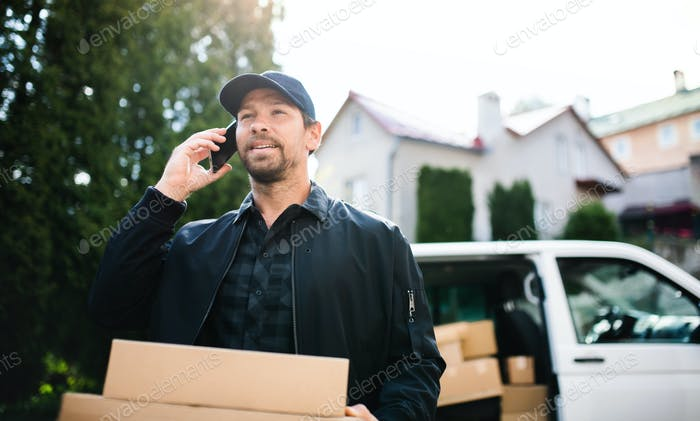Delivery man courier delivering parcel box in town using smartphone