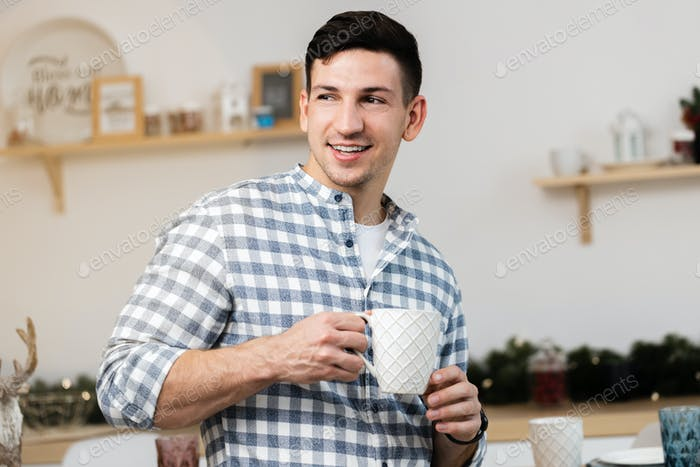 Young man drinking hot drink in kitchen