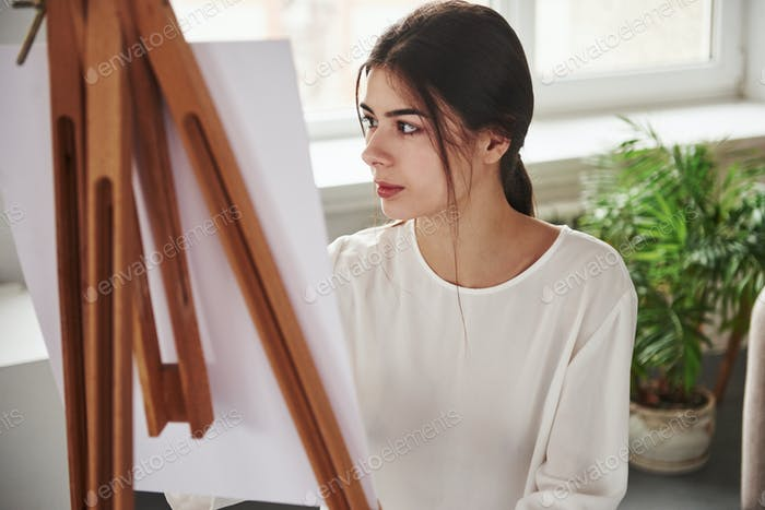 Young brunette in the room with white walls and daylight that comes from the window