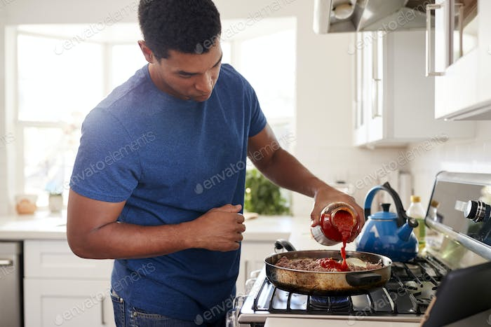 Young adult black man standing in the kitchen cooking on the hob