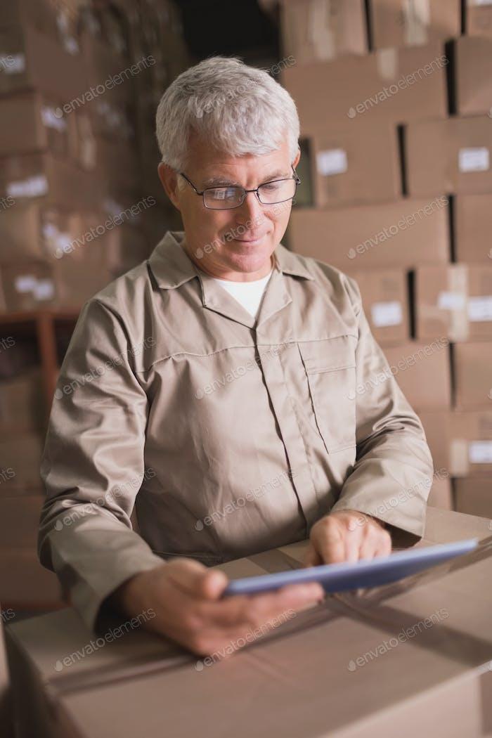 Warehouse worker using digital tablet in warehouse