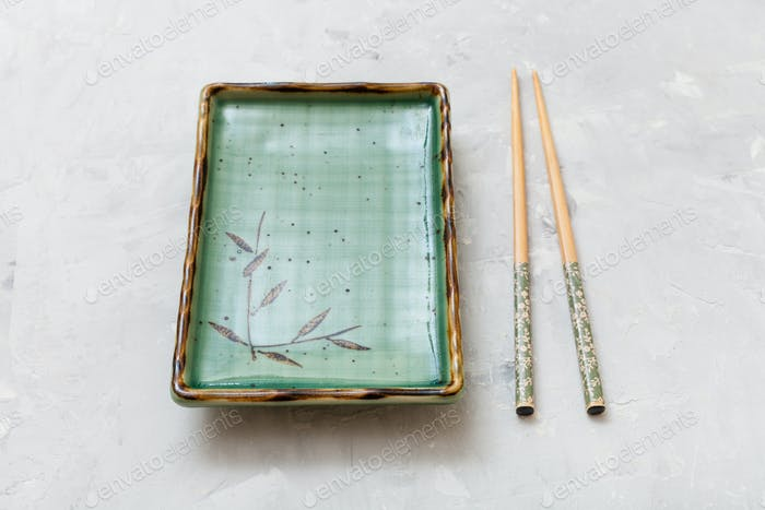 green plate and chopsticks on gray concrete